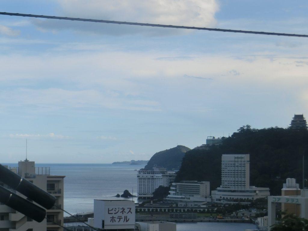 熱海駅付近の車窓から見える温泉街と熱海城